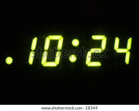 A desk alarm clock with bright green numbers in the dark.