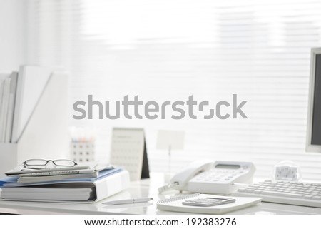 A desk holding a computer, telephone, and notebooks. - stock photo