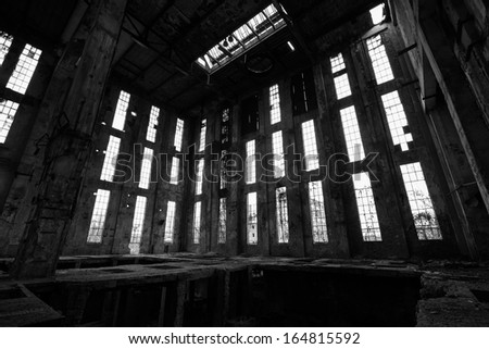 a desolate old industrial building inside, black and white - stock photo