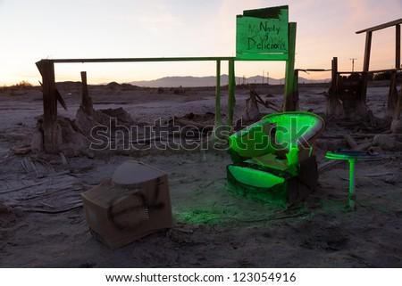 A desolate Salton Sea post-apocalyptic scene of a broken chair in front of a TV shining a green light in the Salton Sea ruins. - stock photo