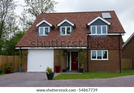 A detached house with an overcast sky - stock photo