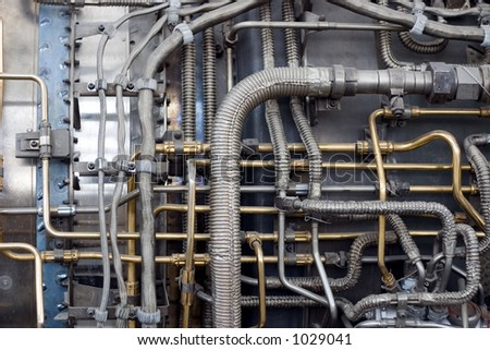 A detail closeup of a series of pipes in a jet engine with cables and connectors. Very technical and complicated. - stock photo