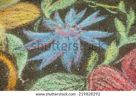 A detail of a child's colourful chalk picture on the pavement - stock photo