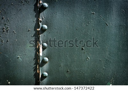 A detailed close up macro photograph of riveted metal painted blue or green.  A great texture image for a background or overlay. Room for Copy.