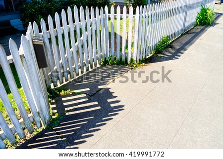 A diagonal view of a weathered white picket fence.