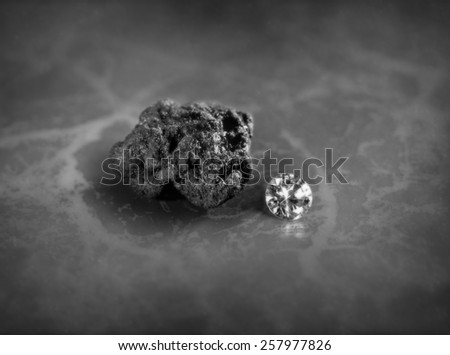 A diamond and a piece of coal on a slate background - stock photo