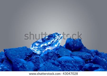 A diamond in a pile of coal shows a long awaited precious gem evolve.  Image was shot using blue backlighting to give it a special effect. - stock photo