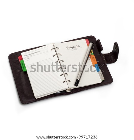 "A diary opened at page of ""Projects"" with pen that hold on it. Isolated on white background - stock photo"
