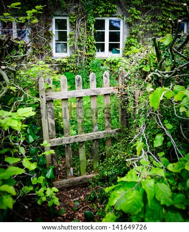 A dilapidated cottage gate with quaint cottage in the background in England, UK at summertime - stock photo