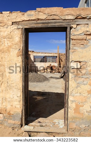 A dilapidated doorway frames the ruins of an old building at the Acoma Pueblo in New Mexico. - stock photo