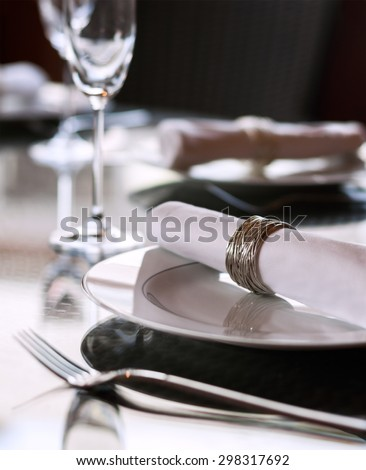 A dining table scene with focus on the napkin ring with plenty of copy space. - stock photo