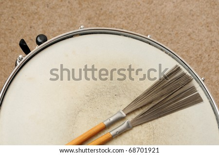 A direct overhead above view of a snare drum on a stand with drum brushes - stock photo