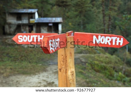 A direction pole paint with North, East, South, is setting up in front of a stone house, 2 direction plates are redundant - stock photo