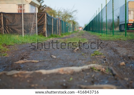 a dirt road leading in allotments between the fences - stock photo
