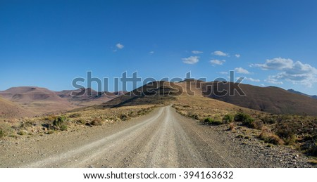 A dirt road stretches off into the mountainous horizon in the Eastern Cape, South Africa - stock photo