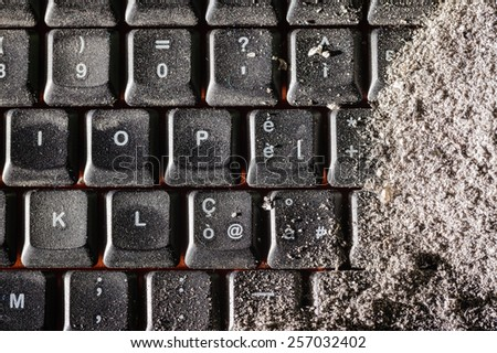 a dirty black keyboard covered in ash or dust