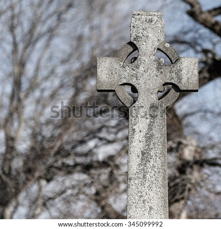A dirty, gray stone Celtic cross in a graveyard. The cross is plain with no marking, and there is some moss on it. Trees are in the background. Color saturation is low. Room for text on the left. - stock photo
