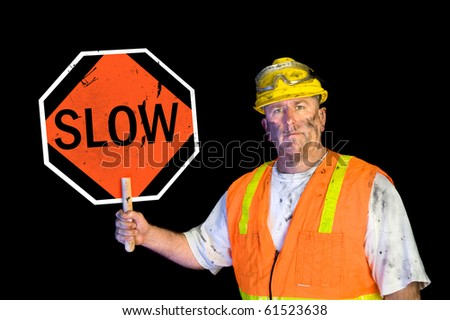 A dirty, greasy utility construction worker with a yellow hard hat, safety goggles, and a reflective orange vest holding up a warning slow sign.