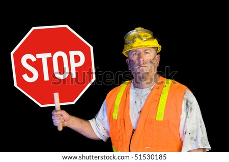 A dirty, grungy, greasy utility construction worker with hard hat, orange vest and eye protection holds up a stop sign.  Isolated on black and can be used as a design element. - stock photo