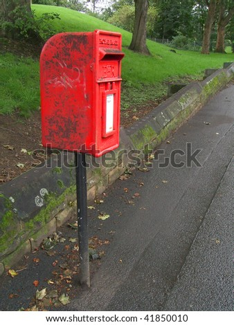 a dirty small British post box on a rainy day - stock photo