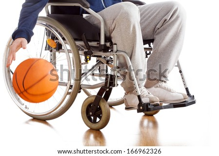 A disabled basketball player in a tracksuit with a ball - stock photo