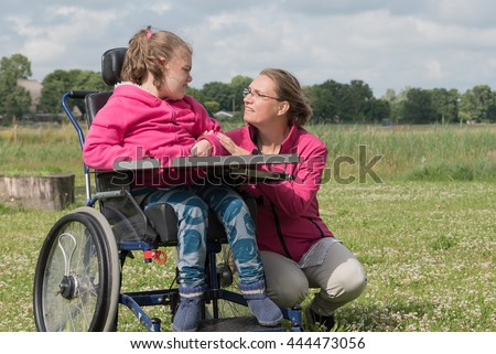 A disabled child in a wheelchair relaxing outside together with a carer / Working together with disability - stock photo