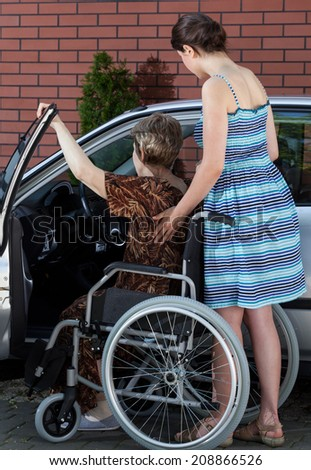 A disabled elderly woman getting into a car with the help of her daughter