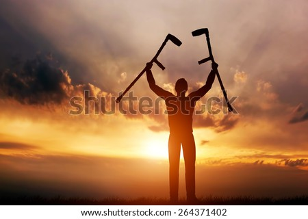 A disabled man raising his crutches at sunset. Positive concept of cure, recovery, medical miracle, hope, insurance etc.  - stock photo