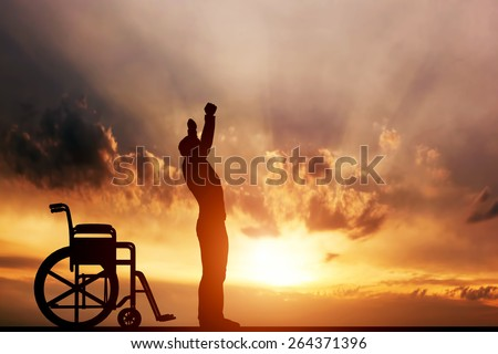 A disabled man standing up from wheelchair at sunset. Positive concept of cure, recovery, medical miracle, hope, insurance etc.  - stock photo