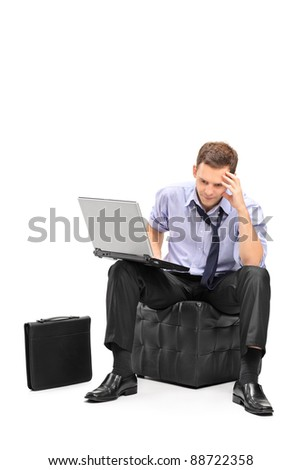 A disappointed businessman and his laptop isolated on white background - stock photo