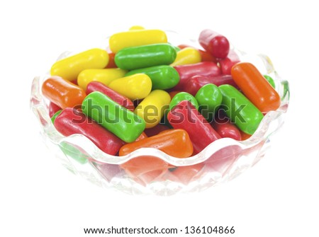 A dish filled with fruit flavored gum on a white background.