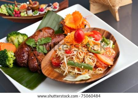 A dish of freshly prepared Thai sausage and som tum green papaya salad. - stock photo