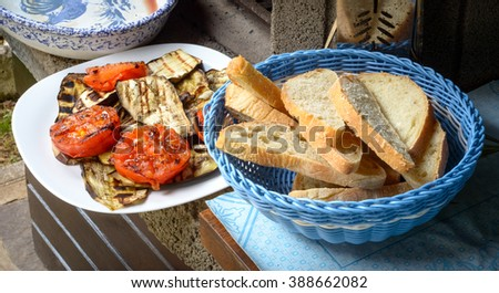 A dish of grilled tomatoes, zucchini and eggplants and a chest of bread for bruschetta - stock photo