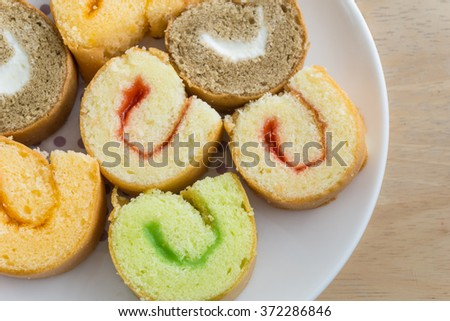 A dish of jam roll cakes on wooden table - stock photo