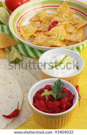 A dish of nachos covered in melted cheese and jalapeno peppers. With dishes of salsa and sour cream and tortillas at the side. Garnished with lime and chilies.