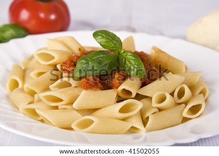 A dish of rigatoni with tomato sauce and basil. - stock photo