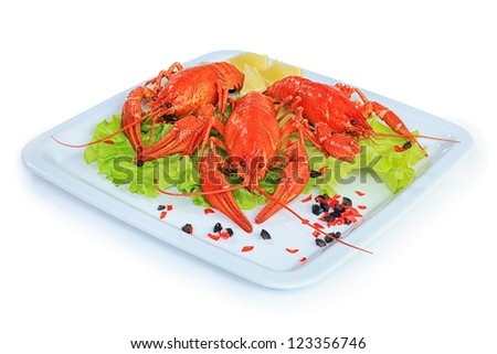 A dish with boiled crawfish, lemon and lettuce. - stock photo