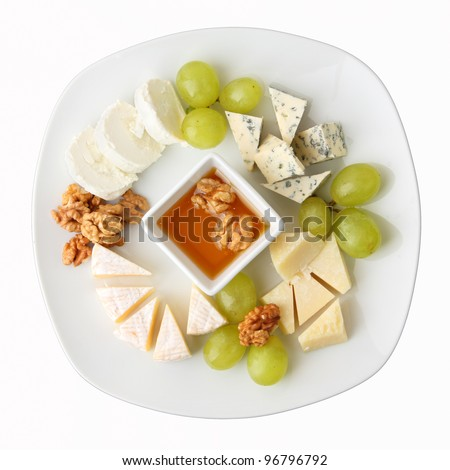 A dish with four kinds of cheese, grapes, walnuts and honey. Top view. - stock photo