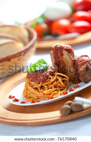 A dish with italian spaghetti with neapolitan ragu sauce and pork and veal meat behind. Shallow depth of field on the pasta course. - stock photo