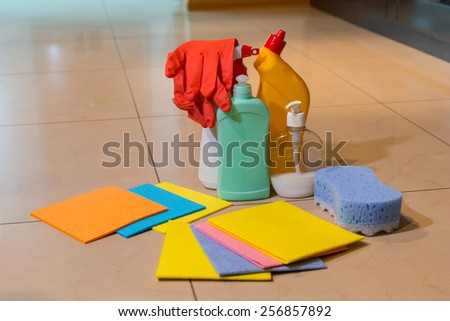 A display of a variety of household cleaning products on a tiled floor including new absorbent cloths, a sponge, gloves and various containers, with copyspace - stock photo