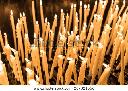 A display of many candles burning in Lourdes - stock photo