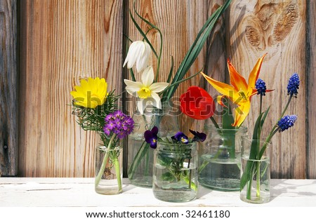 A display of spring multicolored flowers in glass jars on wood background - stock photo