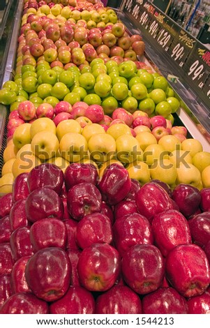 A display of various types apples at a market - stock photo