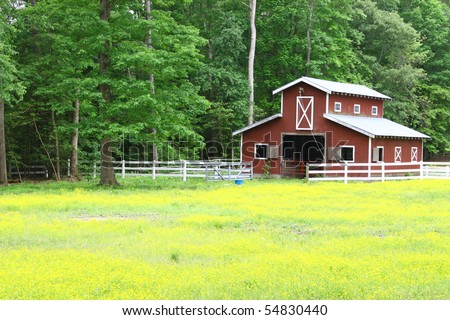 A distant view of a farmers barn in the field with room for your text - stock photo
