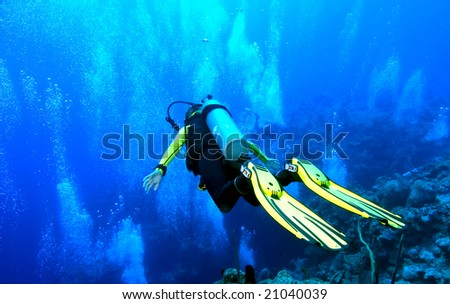 A diver is in 'free fall' position, gliding over the edge of an abyss that drops to 6000 ft! Shot on the wall of Grand Cayman against a backdrop of copious bubbles from divers below. - stock photo