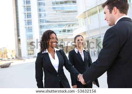 A diverse attractive man and woman business team handshake at office building - stock photo