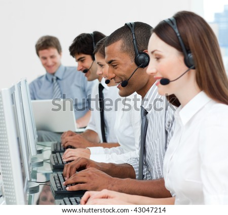 A diverse business group with headset on working in a call center - stock photo