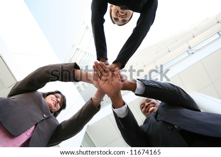 A diverse business team with hands together at company - stock photo