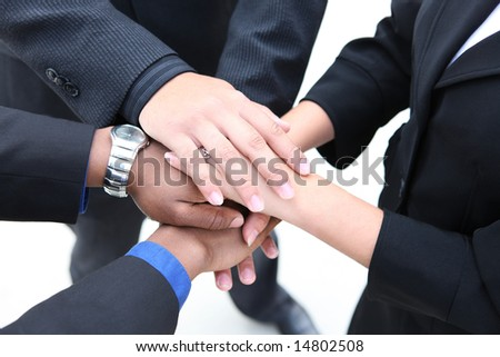A diverse group of workers with their hands together in form of teamwork - stock photo