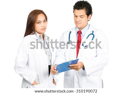 A diverse latino male, asian female team of doctors, one looking at camera while other is listening, reviewing, discussing medical charts diagnosis with serious, studious expressions. Horizontal - stock photo